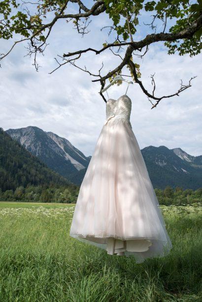 hochzeitsfotograf lichtet brautkleid vor bergen und blauem himmel ab