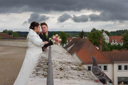 fotograf hällt paar bei romantischem ausblick von burg fest brautstrauß und Taube